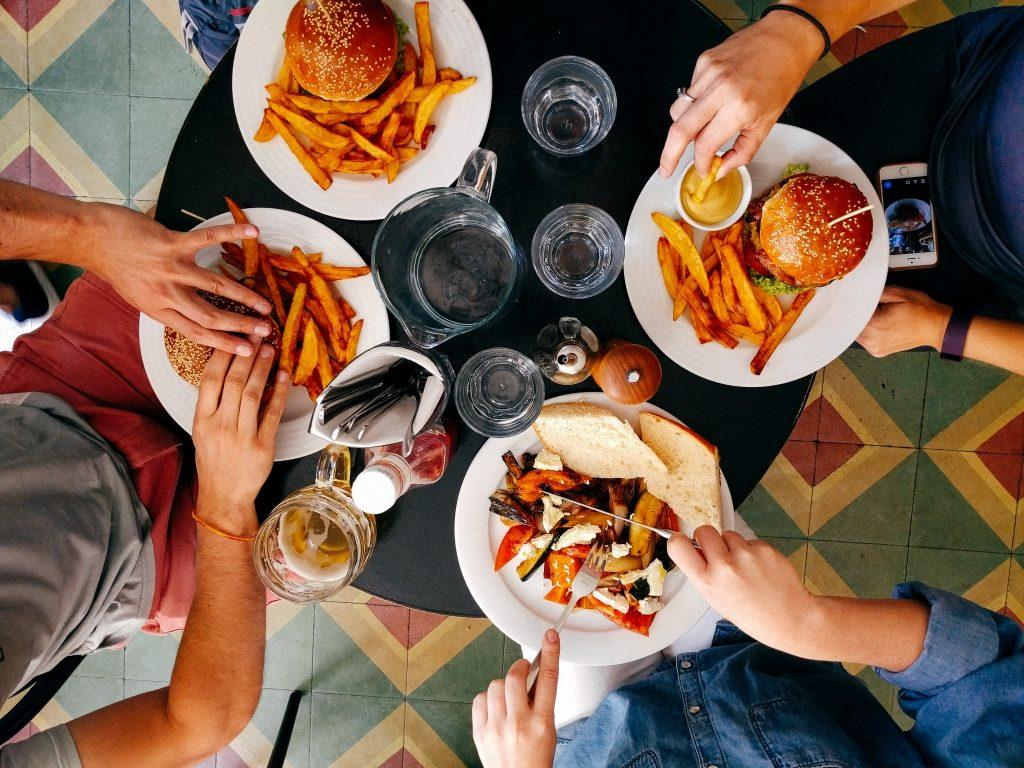 Backpacker sitzen am Tisch und essen Burger